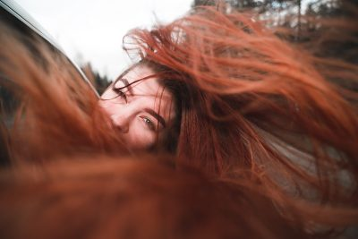 Mistakes That Prevent Hair Growth Woman with Red Hair Blowing In Wind