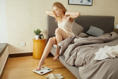 Tips to Lose Weight Quickly Woman Waking Up to Weigh Herself